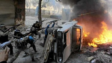 Massive toll ... Free Syrian Army fighters take positions behind a damaged car during an offensive against forces loyal to Syria's President Bashar al-Assad in Aleppo.
