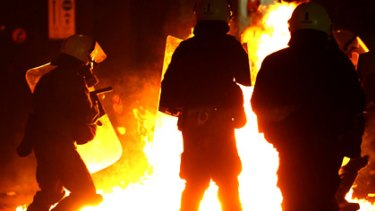 A petrol bomb explodes in front of police during riots in Athens.