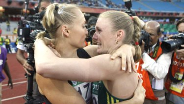 Training partners Andrea Miller (left) and Sally Pearson embrace after winning bronze and gold respectively in the 100m hurdles.