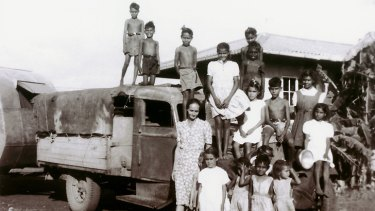 Mixed-race Aboriginal children living at Retta Dixon home in Darwin. Lorna Cubillo, aged about 9, is in the white dress at far right sitting on the bumper over the wheel. Mrs Long, a missionary, is with the children.