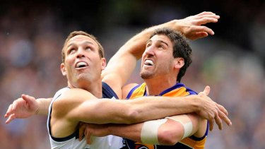 Geelong's Brad Ottens battles with West Coast's Dean Cox in their preliminary final at the MCG.