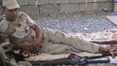 Kurdish Peshmerga fighter takes a break in a farmhouse near Makhmur.