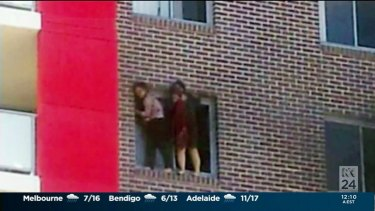 """Yinou """"Ginger"""" Jiang and Pingkang """"Connie"""" Zhang cling to the side of their apartment building before being forced to jump."""