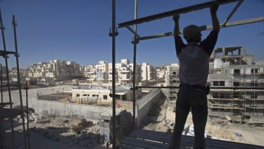 A Palestinian labourer works at a construction site in the West Bank Jewish settlement of Maale Adumim.