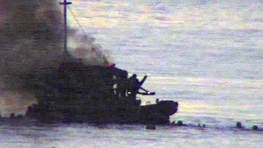 Television pictures show people in the water after the SIEV 36 exploded in flames.