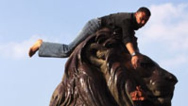 Pride and joy ... Cairenes clean one of the four bronze lions that sit at the corners of the Kasr el-Nile bridge to Tahrir Square.