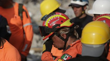 A weary rescue group work in the rubble in Pedernales, Ecuador on Tuesday.