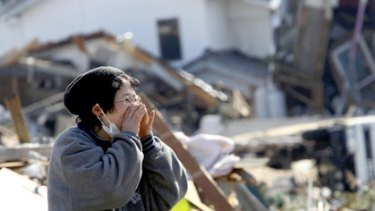 A woman calls for family as she searches ruins in Miyagi prefecture.