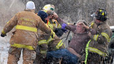 Firefighters rescue a driver beside an icy highway in Delaware.