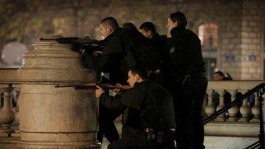 Police with weapons drawn react to suspicious behaviour at Place de la Republique in Paris.