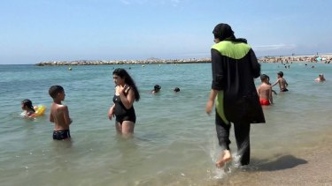 Nissrine Samali, 20, gets into the sea fully clothed in Marseille, southern France. The Cote d'Azur city of Cannes has banned full-body swimsuits dubbed 'burqinis'.