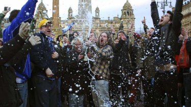 Revellers spray a bottle of champagne in Glasgow.