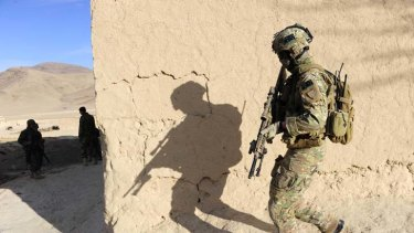 On alert … an Australian soldier's shadow looms large while on patrol with his Afghan National Army counterparts.