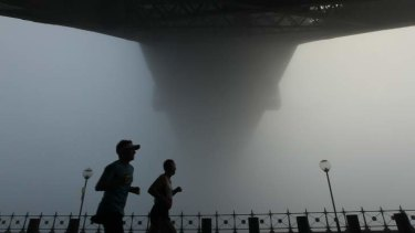 Sydney Harbour Bridge shrouded in fog on Sunday morning.