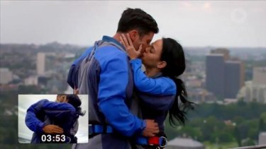 Sam Wood and Nina mash faces en route to the world on-screen kissing record atop the Sydney Harbour Bridge in <i>The Bachelor.</i>