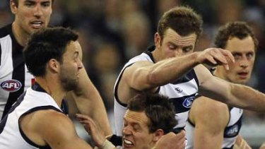 Luke Ball is sandwiched by Cats Jimmy Bartel and Steve Johnson.