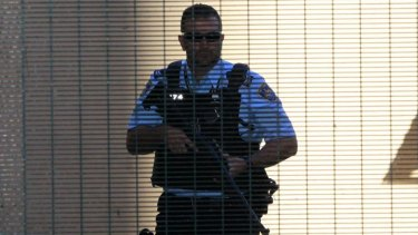 A heavily armed police officer prepares to escort Omarjan Azari at Sydney's Central Local Court.