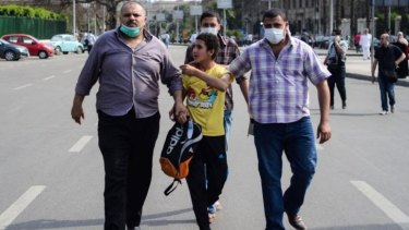 Extra powers: Policemen in plain clothes arrest an Egyptian youth following two explosions at Cairo University on April 14.