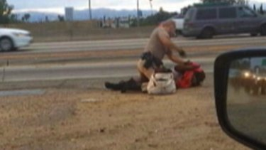 A still from a passing motorist's video shows the confrontation between a California Highway Patrol officer and a woman on a Los Angeles freeway.