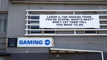 The Club Hotel in Glenorchy, a lower socio-economic area on the outskirts of Hobart, where poker machines are more concentrated than in the affluent areas of the city, displays its political signage.