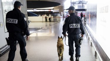 French police officers and a sniffer dog patrol a terminal building at Charles de Gaulle airport on Thursday.