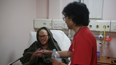 A family member gives water to Liang Sheng-yueh at the Grande Hospital in Kathmandu.