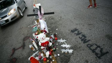 A makeshift memorial sits in the middle of the street where 18-year-old Michael Brown was shot and killed by police in Ferguson, St Louis.