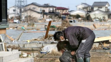 Home and broken-hearted: a couple returns to a quake-shattered home in Watari, Miyagi prefecture.
