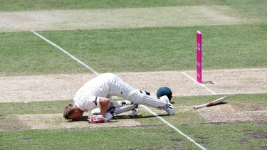 David Warner kisses the ground in tribute to Phillip Hughes after reaching 63 not out.