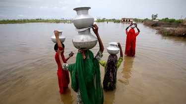 Girls wade through floodwaters in Pakistan's Sindh province.
