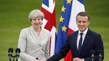 French President Emmanuel Macron shakes hands with British Prime Minister Theresa May.