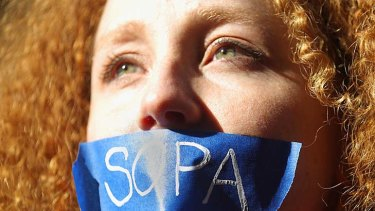 Protester Nadine Wolf demonstrates against the proposed Stop Online Piracy Act (SOPA) and Protect IP Act (PIPA) outside the offices of US Senators Charles Schumer and Kirsten Gillibrand in New York City.