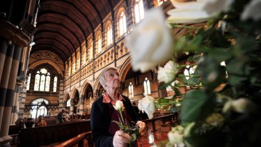 Jeanette Skipper arranges flowers for the Jim Stynes funeral at St Paul's Cathedral today.