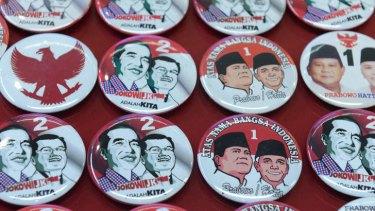 Pins featuring presidential candidates Joko Widodo-Jusuf Kalla and Prabowo Subianto-Hatta Rajasa.