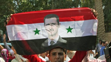 A Syrian man shows support for President Assad during a government-guided tour.