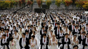 Couples from around the world join in a mass wedding ceremony in 2009 arranged by the Reverend Sun Myung Moon's Unification Church at Sun Moon University in Asan, South Korea.
