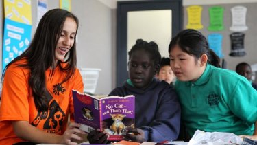 Antonia Horafiaris, 15, of East Malvern, reads yesterday to Veronica Dador, 9, and Kelly Huynh at Sacred Heart Primary School in Fitzroy.