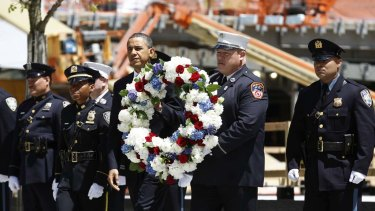 US President Barack Obama carries a wreath accompanied by New York City firefighters and NYPD police officers during a wreath laying ceremony at the National September 11th Memorial at the World Trade Centre.