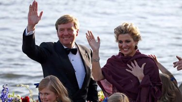 Dutch King Willem-Alexander and Queen Maxima wave during a boat parade in Amsterdam.