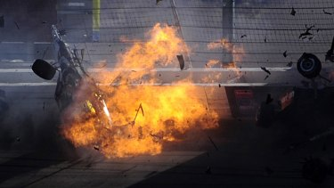 Dan Wheldon's car bursts into flames after being hit in a 15-car pile-up in the Las Vegas IndyCar race.