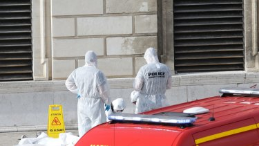 Investigative police officers work at a body outside Marseille 's main train station.