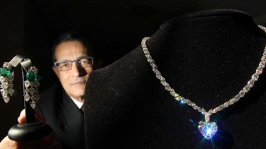 Glimmer of hope ... Sotheby's head of jewellery, Hamish Sharma, with a pair of Bulgari diamond and emerald earrings and a 24-carat diamond necklace.