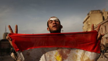 An anti-government demonstrator holds a bloodied Egyptian flag after a deadly battle with regime supporters in Tahrir Square, Cairo.