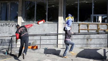 Protesters hurl items at the building.