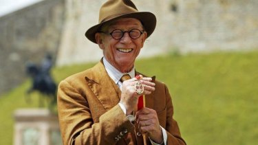 British actor John Hurt holds his award of a Knighthood presented by Britain's Queen Elizabeth II during an Investiture ceremony at Windsor Castle, England.