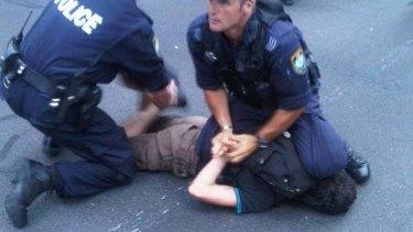 Police subdue a protester.