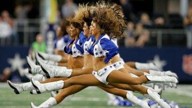 Hair-raising routine: The Dallas Cowboys cheerleaders perform before a match.