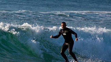Opposition leader Tony Abbott rides a wave at Manly at 7.23am today.