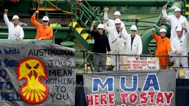 Defiant ... crew members of the Araluen Spirit at Shell's Gore Cove terminal yesterday. Shell promised talks with the crew and the Maritime Union of Australia.