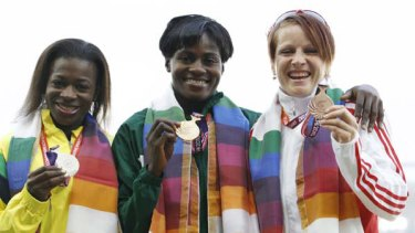 Silver medallist Natasha Mayers of Saint Vincent and the Grenadines (left to right), gold medallist Osayemi Oludamola of Nigeria and bronze medallist Katherine Endacott of England pose with their medals for the women's 100 metres event.